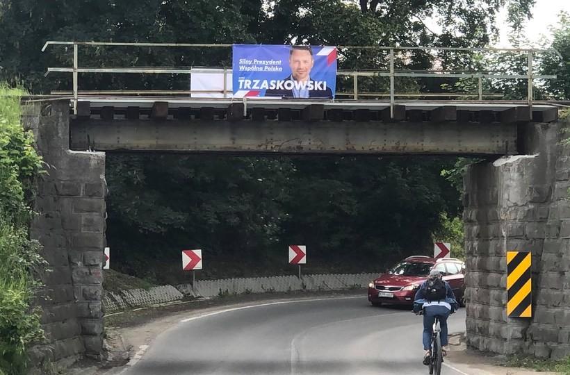 Barwy kampanii. Banery kandydata na prezydenta huśtają się na wiadukcie kolejowym